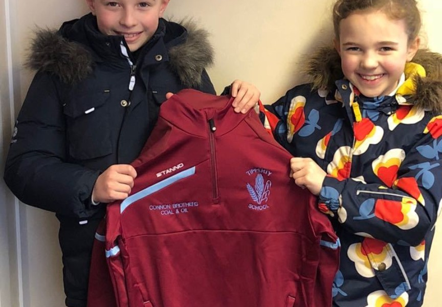 Lilly and Harris from Tipperty School show off their new football training tops sponsored by Connon Brothers